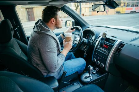 angry man driving car and drinking coffee. traffic collapse