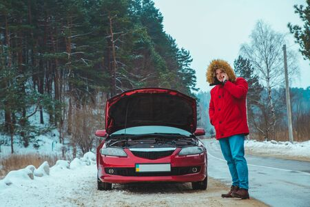 man standing near broken car at roadside snowed winter weather