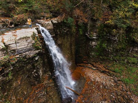 woman on the cliff looking at waterfall enjoying the view autumn time