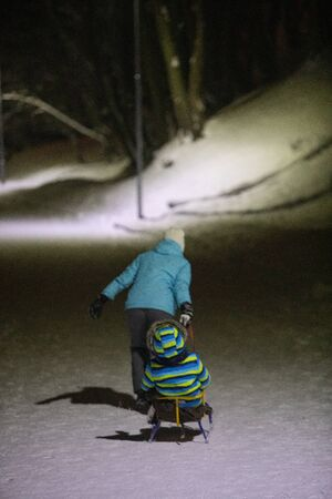 mother pulling sled with kid by winter city park night lights