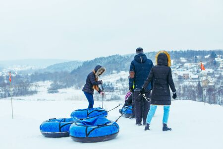 LVIV, UKRAINE - January 7, 2019: family ride down by snowing hill with snow tube. winter time