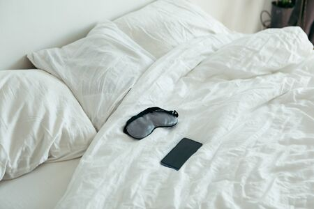 sleeping mask with phone at bed with white sheets sunny morning bedroom Banco de Imagens