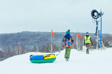LVIV, UKRAINE - January 7, 2019: children sliding snow tube down by snowed hill. winter activity