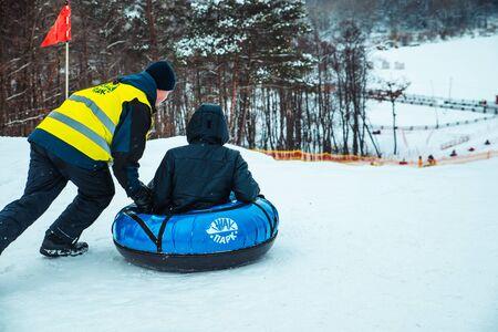 LVIV, UKRAINE - January 7, 2019: winter fun activities. ride down by hill on snow tubing. pushing 에디토리얼