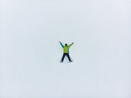 overhead view of man making snow angel copy space