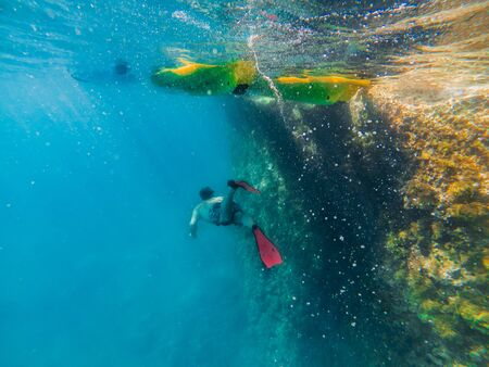man in underwater in flippers looking at sea bottom summer beach vacation