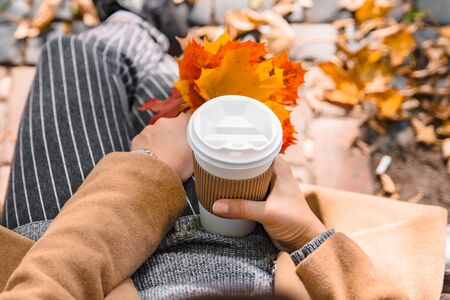 woman holding coffee cup drink to go autumn fall season yellow leaves