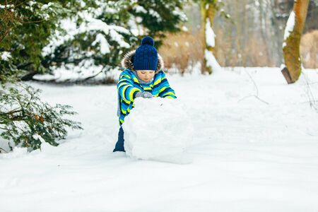 petit garçon mignon faisant un bonhomme de neige. faire rouler une grosse boule de neige