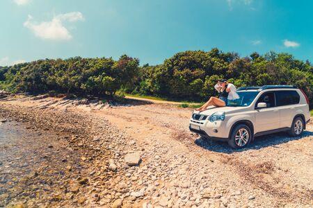 女人坐在汽车引擎盖在夏天的海滩度假概念旅行时间