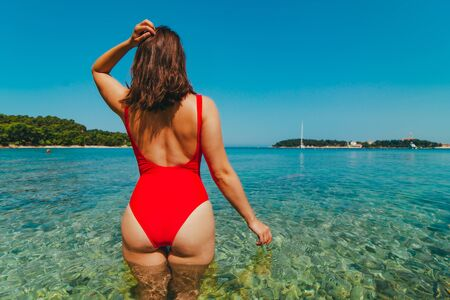 woman in red swimsuit standing in sea water. coastline yacht on background