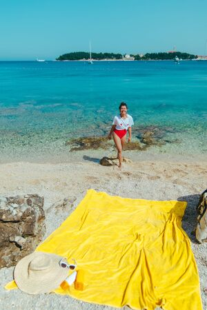 young pretty woman in red swimsuit and white t-shirt at sea beach