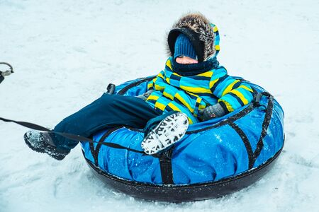 little kid in snow tube. winter time activities 写真素材