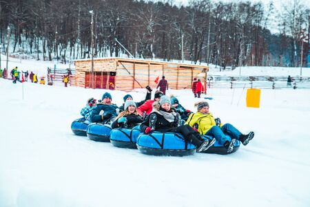 LVIV, UKRAINE - January 7, 2019: winter fun activities. ride down by hill on snow tubing. pushing 新聞圖片
