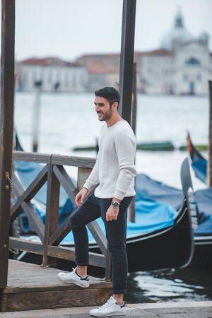 Venice, Italy - May 25, 2019: man modeling at city dock pier fashion