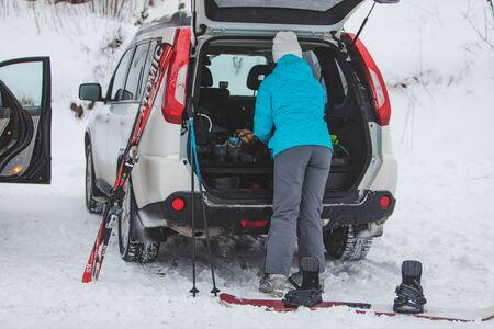 KAZKOVA POLYANA, UKRAINE - January 26, 2019: woman gathering to ski. car with opened trunk. parking