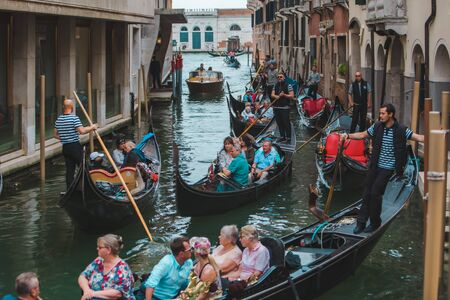 Venice, Italy - May 25, 2019: view of gondolas traffic in canal singer at boat summer vacation