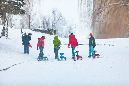 Lviv, Ukraine - January 5, 2019: kids boys friends pulling sledge to the snowed hill winter fun time