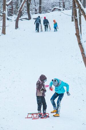 Lviv, Ukraine - January 5, 2019: kids sliding from snowed hill winter time