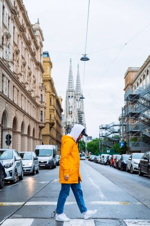 woman crossing street old church towers on background vienna austria