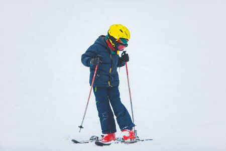 little kid learning to ski. winter sport activity
