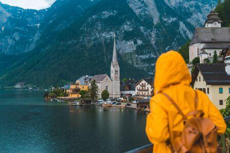 vrouw in gele regenjas kijkend naar het panoramische uitzicht op de stad Hallstatt