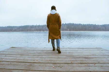 autumn lake season woman in coat at wooden pier fall