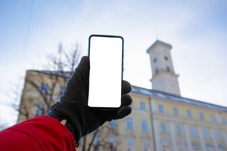 man hand in gloves holding phone with white screen lviv city hall on background copy space travel concept 版權商用圖片