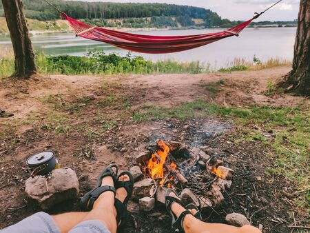 couple resting near campfire looking at lake hammock on background