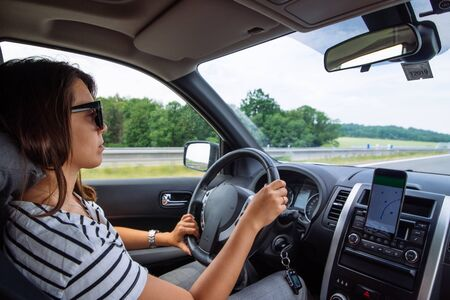 woman driving car by speedway summer time navigation on phone