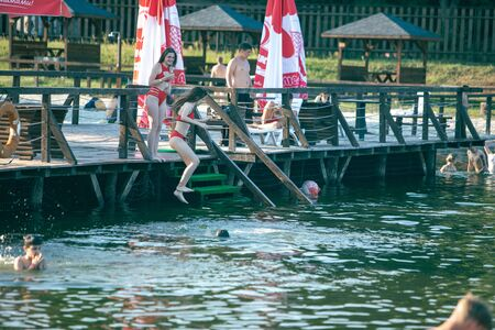 girls jumping from pier to lake water summer time 版權商用圖片
