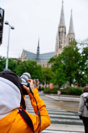 woman with professional camera taking picture of old gothic church vienna austria 版權商用圖片