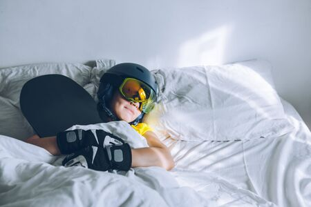 woman sleeping in bed with snowboard dreaming about ski at snow mountains Stok Fotoğraf