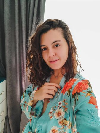 young pretty woman taking selfie picture in domestic outfit nightie Stock Photo