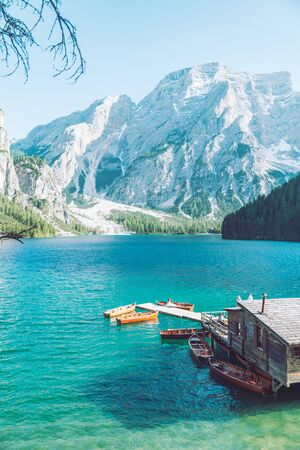 view of wooden house on water with pier and boats lake in dolomites mountains. hiking place
