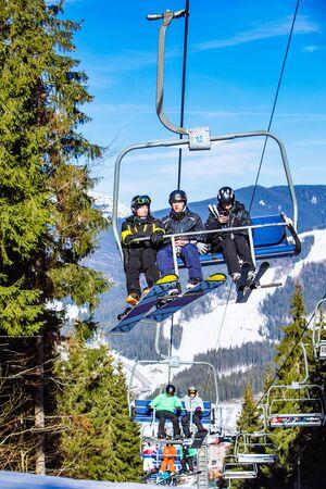 BUKOVEL, UKRAINE - February 10, 2019: people at ski lift in mountains. winter sport activity