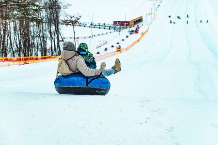 parent with kid sliding down by snowed hill with snowing tube. winter leisure Standard-Bild - 139601877