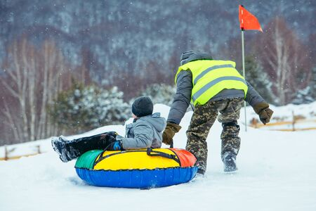 winter fun activities. ride down by hill on snow tubing. pushing Foto de archivo - 140117650