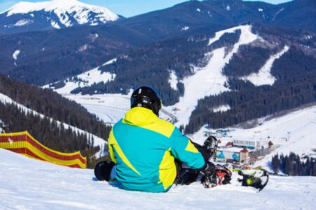 man sitting with snowboard on the top of the hill with beautiful view. copy space. sunny day