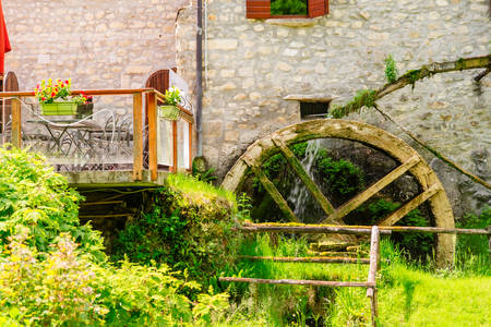 view of old stone building with shutter on windows and water mill copy space