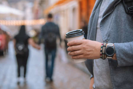 man hand close up holding disposable coffee cup smart watch with bracelet on wrist Banque d'images - 151547104