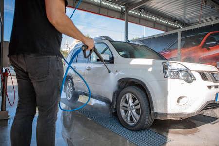 strong man washing car at self carwash outdoors summer time Banque d'images - 151547230