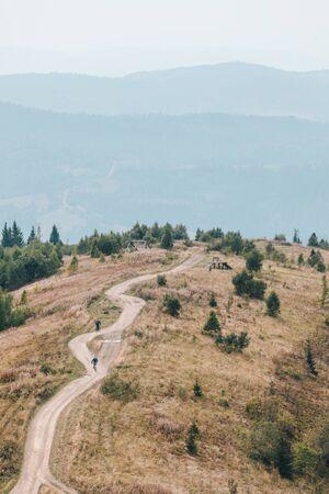 Zakhar Berkut, Ukraine - September 7, 2019: people riding on all terrain vehicle by mountains autumn summer time