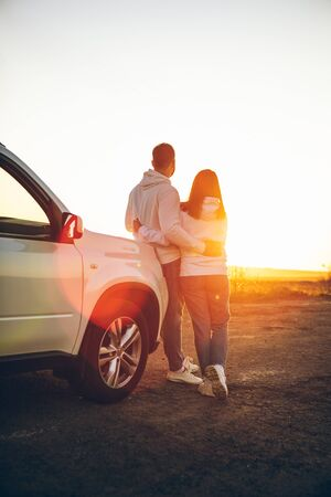 romantic moment couple looking on sunset near white suv car copy space. 写真素材 - 143236265
