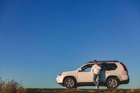 man standing in front of white suv on sunset. car travel concept. golden hours