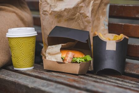 fast food. big burger with cup of tea on a bench. eat and go