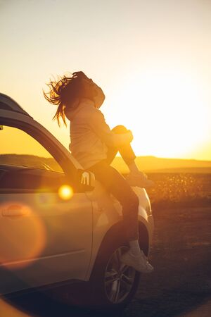 woman stop at roadside to enjoy sunset. sitting on car hood. copy space 写真素材 - 143236166