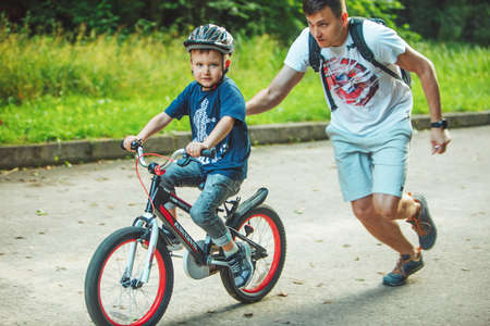 Lviv, Ukraine - June 23, 2019: father teaching son how to ride bicycle. summer time. public park
