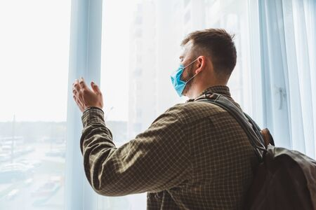 man in medical mask standing near window at home with backpack