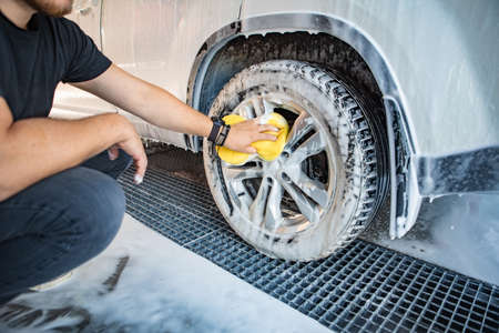 man cleaning car with yellow sponge. carwash concept. copy space