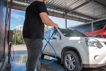strong man washing car at self carwash outdoors summer time